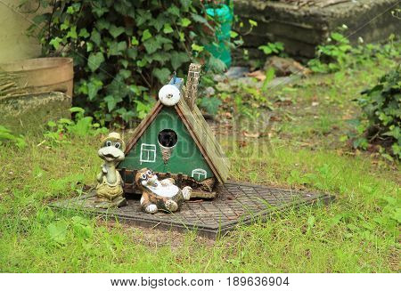 little garden statues, frog and mole, in front of their tiny house in the garden