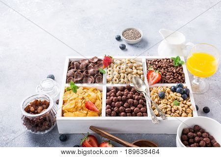 Variety of cold quick breakfast cereals with berries in white wooden box, healthy eating for kids, selective focus.