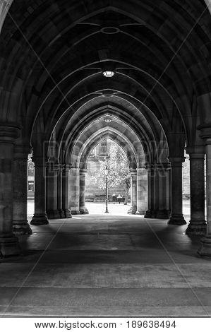 Arcades of old Glasgow University corridor cloisters. UK Scotland. Black and white image.
