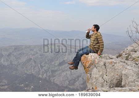 Young man sits on a cliff edge on the top of mountain with gorgeous view and drink water. Enjoying the view on the edge of the cliff