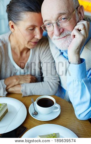 Senior man with grey beard looking at camera with his wife nar by