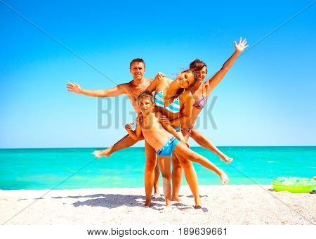 Happy Family Having Fun at the Beach. Joyful Family. Vacation and Travel concept. Summer Holidays. Parents with Child enjoying a holiday at the sea