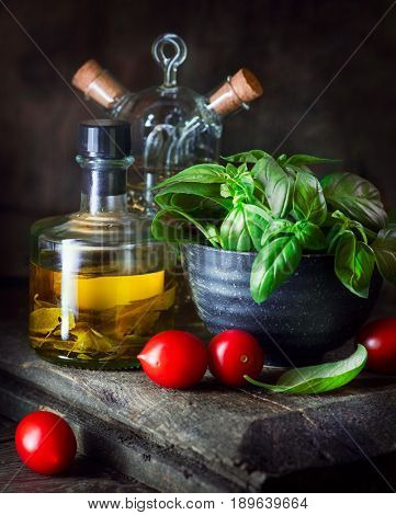 Italian Homemade Food ingredients still life. Olive oil, cherry tomatoes, fresh basil leaves, Parmesan cheese, basil and olive oil. Cooking Pasta. Dinner. Mediterranean cuisine
