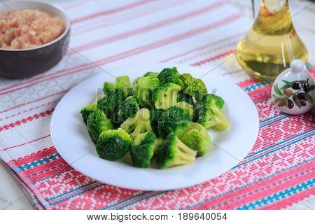 Crude Broccoli On A White Plate On A Light Background