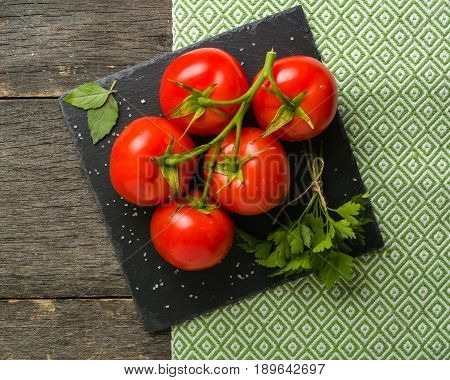 Branch With Five Ripe Red Tomatoes. Drops Of Water On Ripe Fruits. Green Leaves And Trunk.