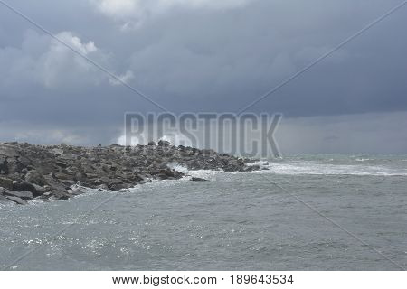Stormy weather at the sea with the sky full of dark Clouds and waves splashing on the rocks
