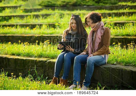 Young women sit at stone steps with the tablet in hands. Girlfriends with interest look at the screen. Pleasant outdoor recreation in spring day. Young green grass and yellow dandelions.