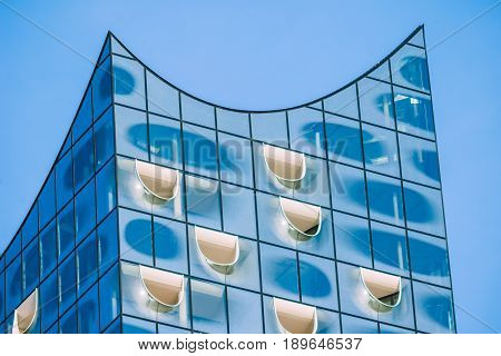 Hamburg, Germany - May 28, 2017: Close up of top shape of Elbphilharmonie with white windows and some white clouds in sky, Hamburg, Germany.