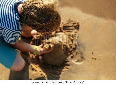 Little boy playing sand by the seashore