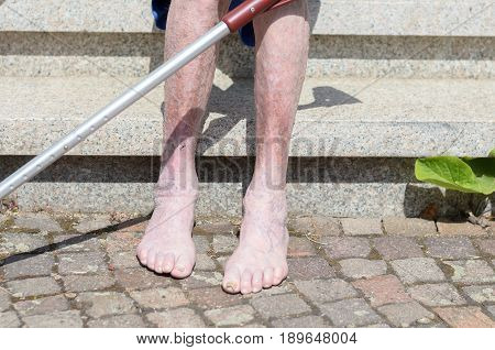 Elderly Barefoot Man Sitting On A Bench Outdoors