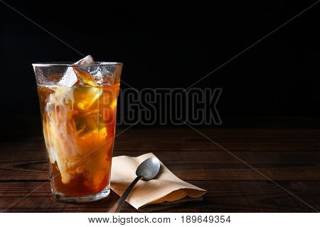 Closeup of a glass of iced coffee on a dark wood table. Fresh poured cream is permeating through the glass with a napkin and spoon lay next to the glass. Horizontal with copy space.