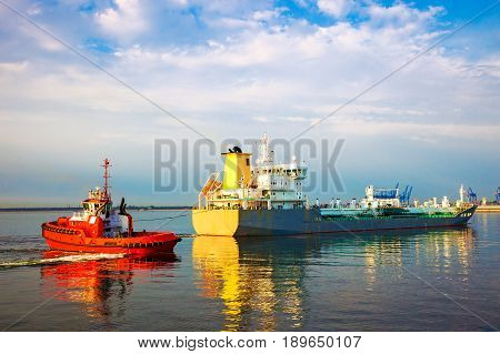 Tugboat towing tanker ship in port .