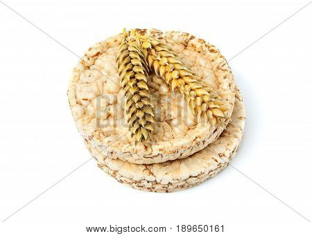 Whole grain crispbread with ear of wheat isolated on white background.