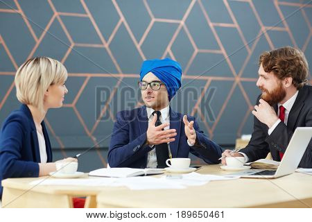 Arabian man in turban giving interview in tv-studio