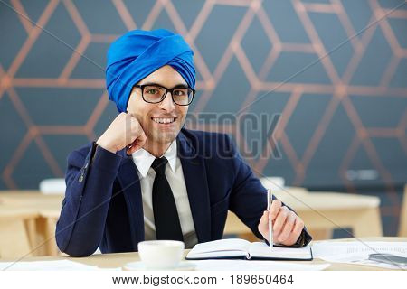 Happy young man in suit and traditional Arabic turban looking at camera