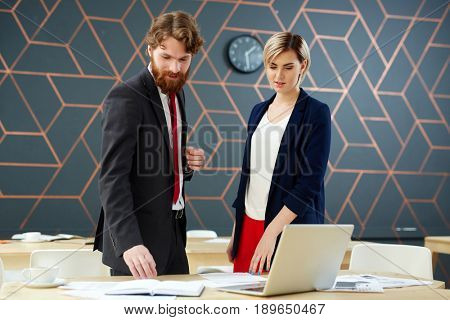 Two newsreaders standing by workplace and discussing notes
