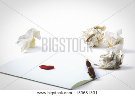 Working with crumpled paper and gift card with heart on table background