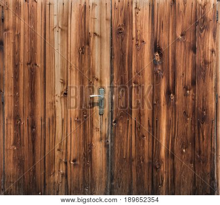 Barn door with handle and rustic wood planks background. Organic Texture.