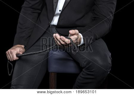 Rich man sitting on bar stool and holding whip bdsm