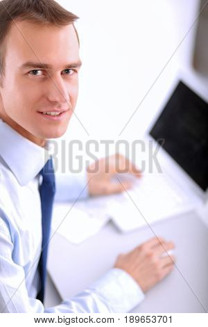 Businessman sitting at table in office lobby,using laptop computer