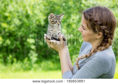 Portrait of a young beautiful woman and kitten. A girl holding a kitten.