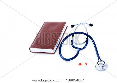 Medical stethoscope and pills near a medical book
