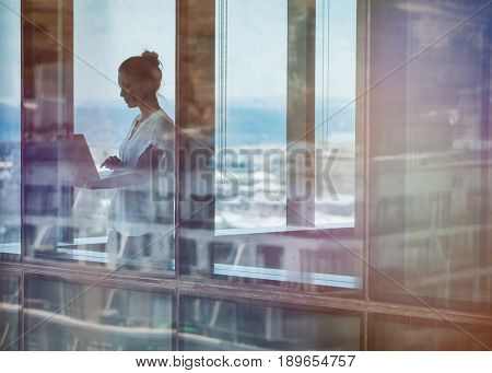 Mature businesswoman standing by window and using laptop. Entrepreneur standing inside office building and working on laptop computer.