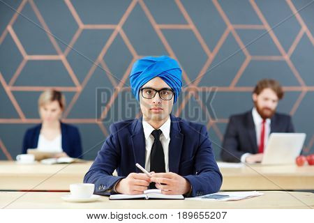 Arabian man in suit and turban looking at camera at workplace
