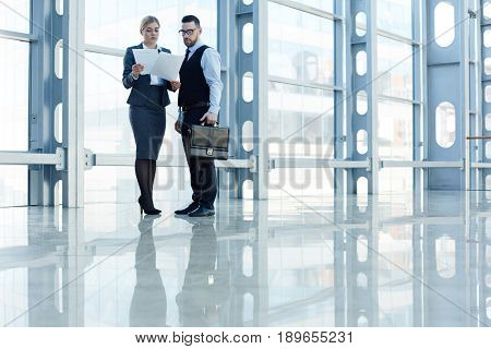 Businesswoman showing papers to ceo while reading them