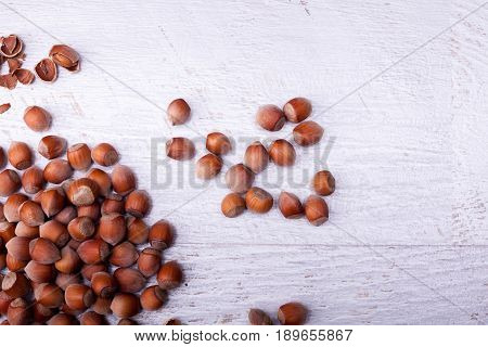 Over top view of Hazelnuts on white wooden background in studio photo. Healhty snacks