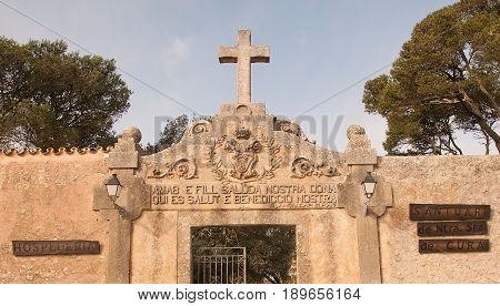 RANDA MALLORCA SPAIN - FEBRUARY 9 2013: Cross and entrance inscription on the monastery Cura on February 9 2013 in Randa Mallorca Spain.