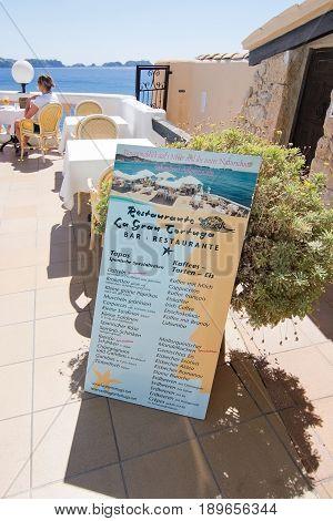 CALA FORNELLS MALLORCA SPAIN - SEPTEMBER 6 2016: Tortuga restaurant menu information board and sea view on a sunny day on September 6 2016 in Cala Fornells Mallorca Spain.