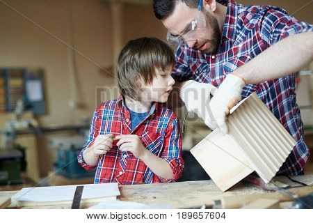 Little boy looking at starling house while his father measuring its length