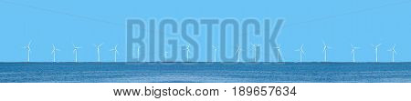 Wind power turbines coastal placement with blue sky and ocean.