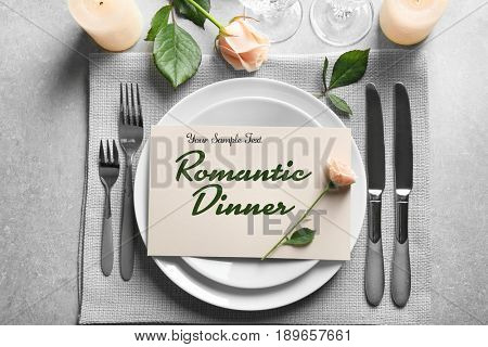 Elegant table setting for dinner. Text ROMANTIC DINNER on card
