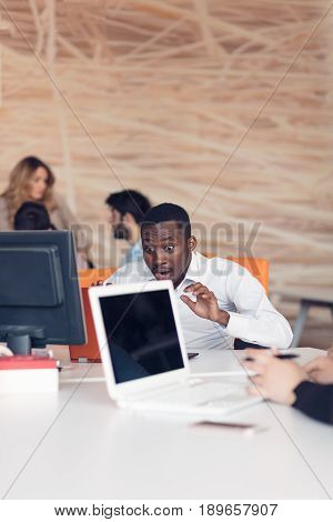 Handsome successful African American looking at the screen with serious face expression at modern startup office.