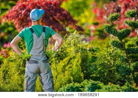 Satisfied Caucasian Gardener in Front of His Beautiful Garden. Garden Works.