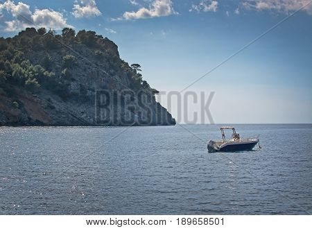Mountainside sea moored boat glitter and horizon in Mallorca Spain.