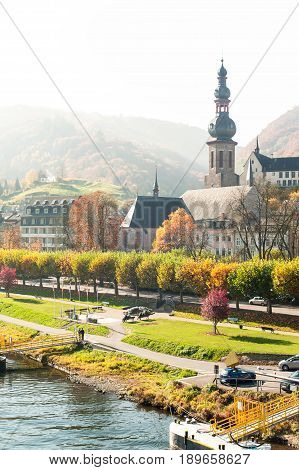 Early morning foggy landscape with town Cochem along the river moselle in rays of sunlight. Panoramic view. Multi-colored vertical outdoors autumn image.