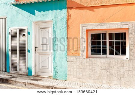 White window and door with stone decoration on vibrant multicolored wall. Canary Islands Tenerife. Spain. Outdoors image.