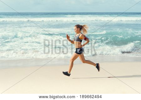 Running young woman on the beach