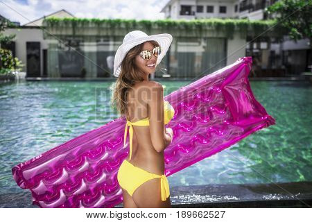 Smiling woman with air mattress