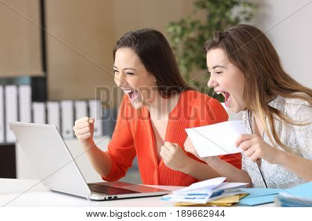 Excited businesswomen reading good news on line in a laptop on a desk at office