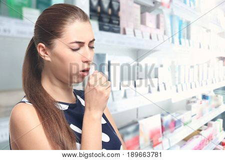 Allergies or cold concept. Young woman coughing at pharmacy