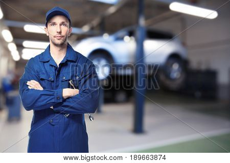 Auto mechanic with tool and workshop on background. Car service concept