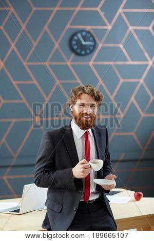 Happy bearded businessman with cup of coffee having break