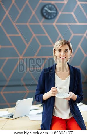 Young businesswoman with cup of tea looking at camera
