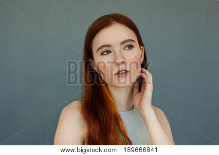 Close up portrait of a beautiful redhead female model with colored strands in hair and green eyes having thoughtful serious look and mouth wide open. Pretty ginger girl posing on blue wall background