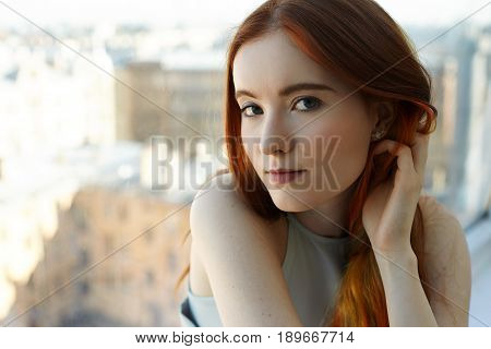 Close up portrait of pretty European appearance teenage girl looking thoughtful and dreamy at camera. Gorgeus redhead student female with colored strands of hair and green eyes on old city background