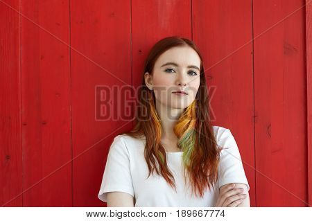 Portrait of confident redhead student female with colored strands in hair dressed in white t-shirt looking at the camera standing on red wall background. Hipster girl posing in studio arms crossed